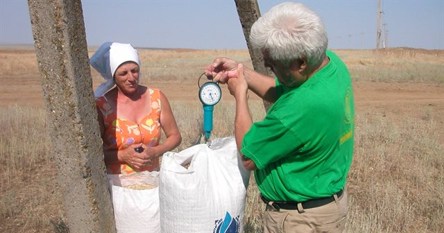 image of project team member collecting seed from local agricultural worker
