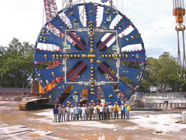 Shot of giant tunnel boring machine dwarfing workers standing in front of it.