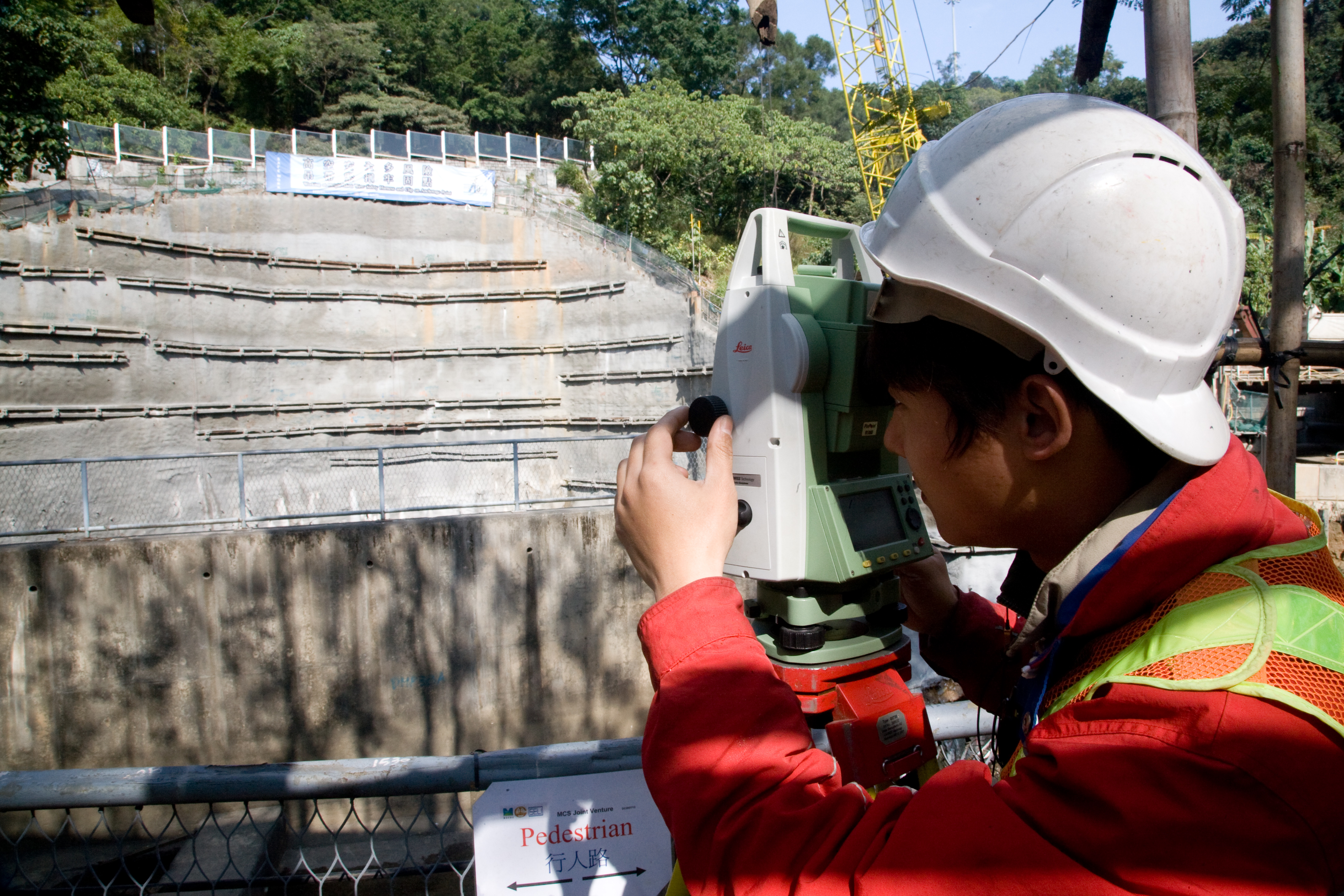 View of site worker taking survey measurements at an intake site