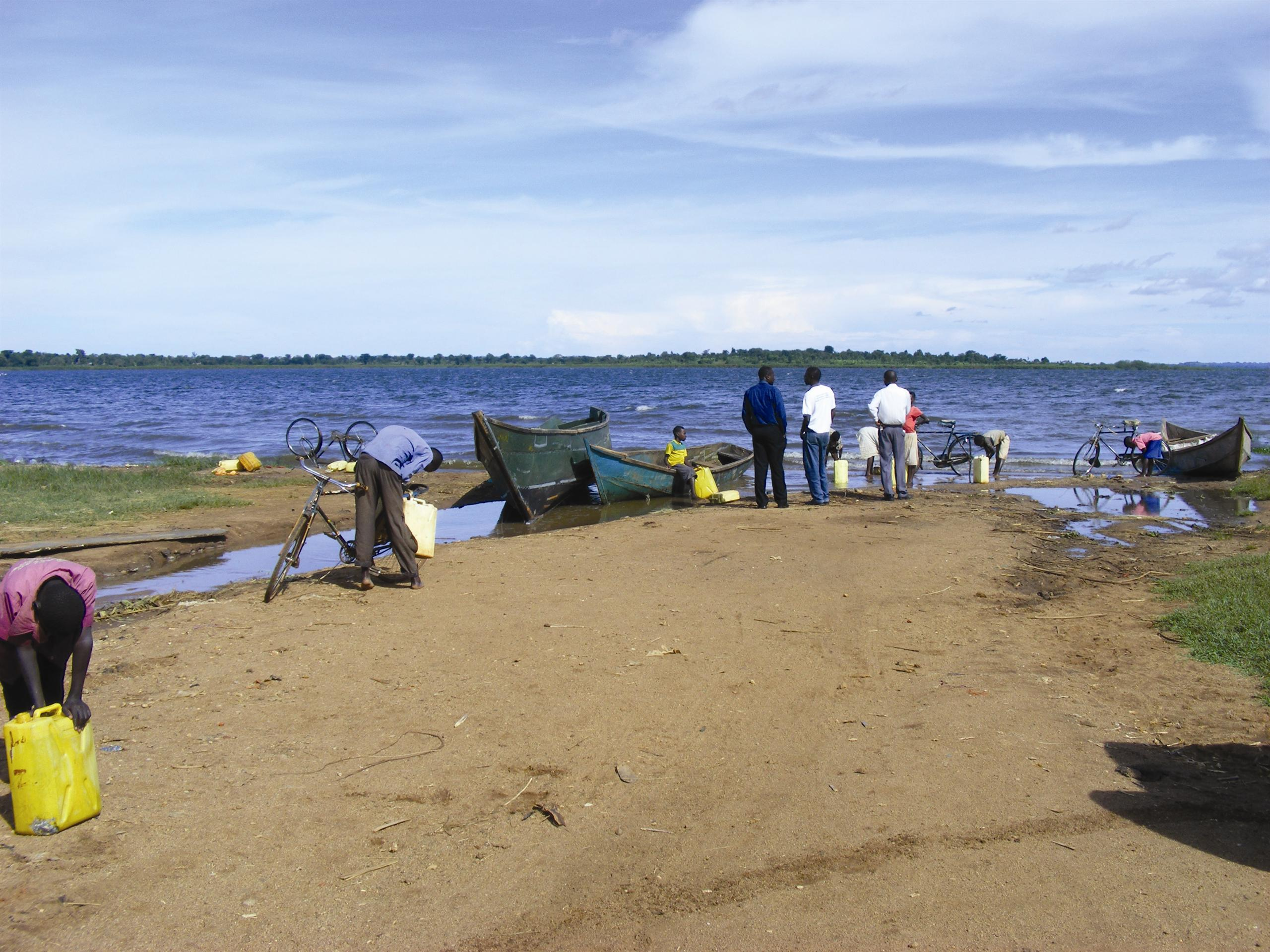 Local people by side of lake with wooden boat on shore