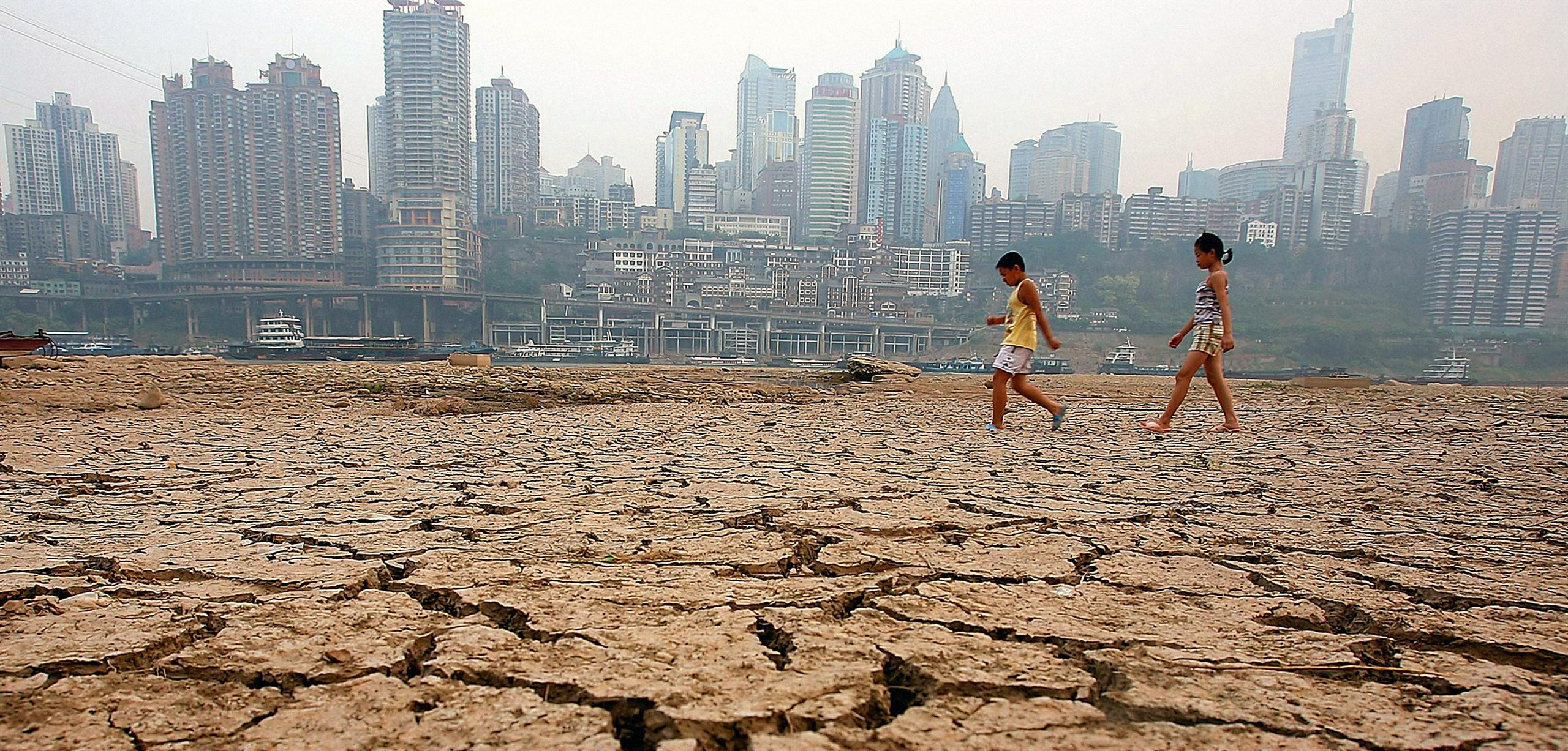 Two young children walking across cracked, dry land with a city skyline behind.