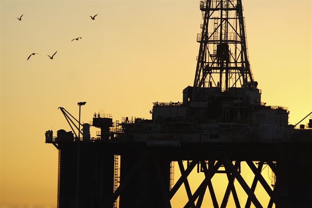shot of oil rig against sunset