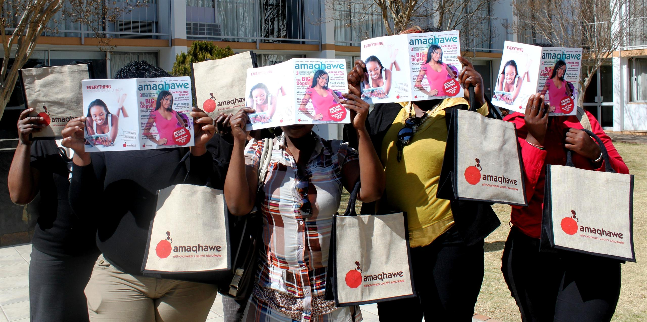 Sex workers hold up the first issue of Amaqhawe magazine