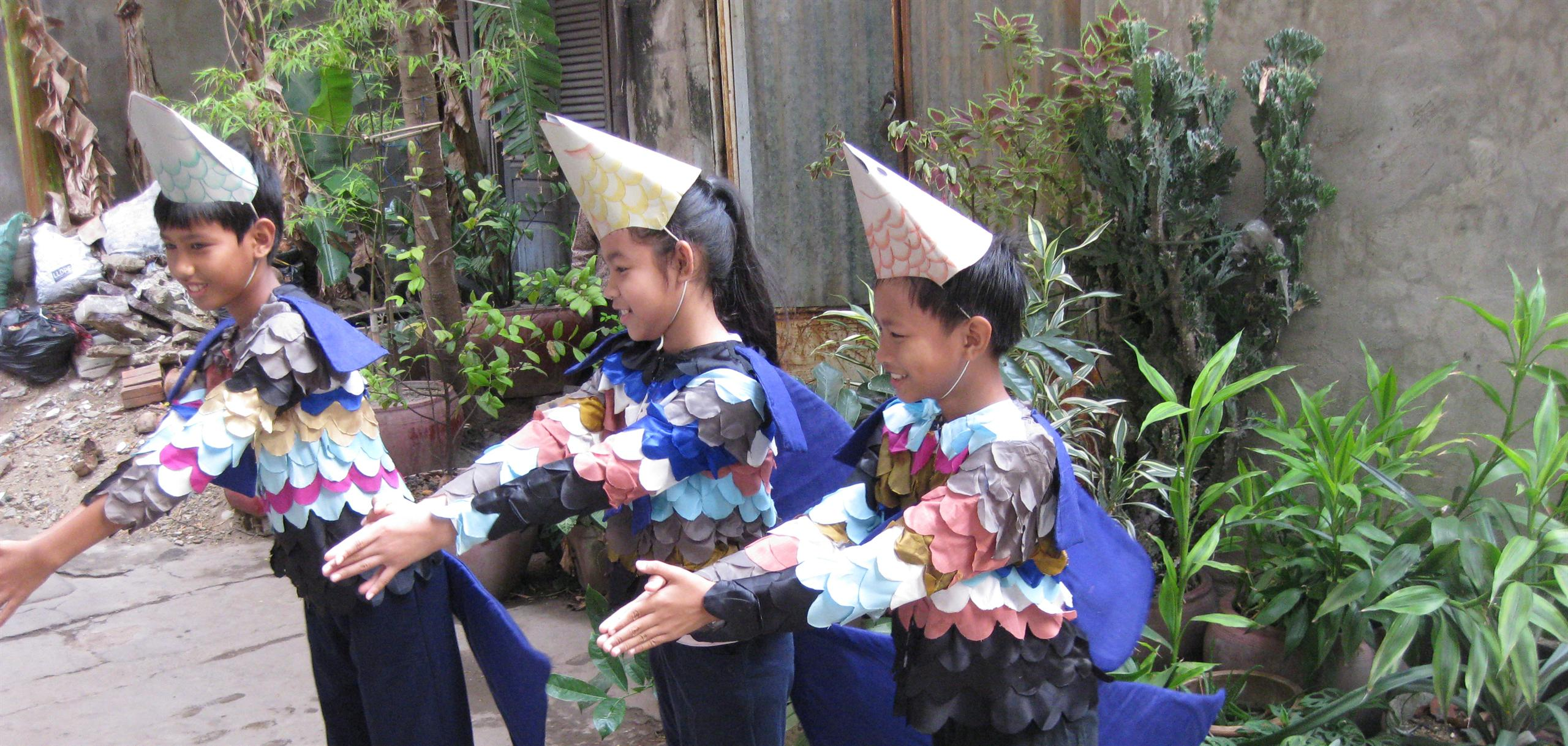 School children act out how to use guppy fish to reduce the breeding of the mosquito that transmits dengue