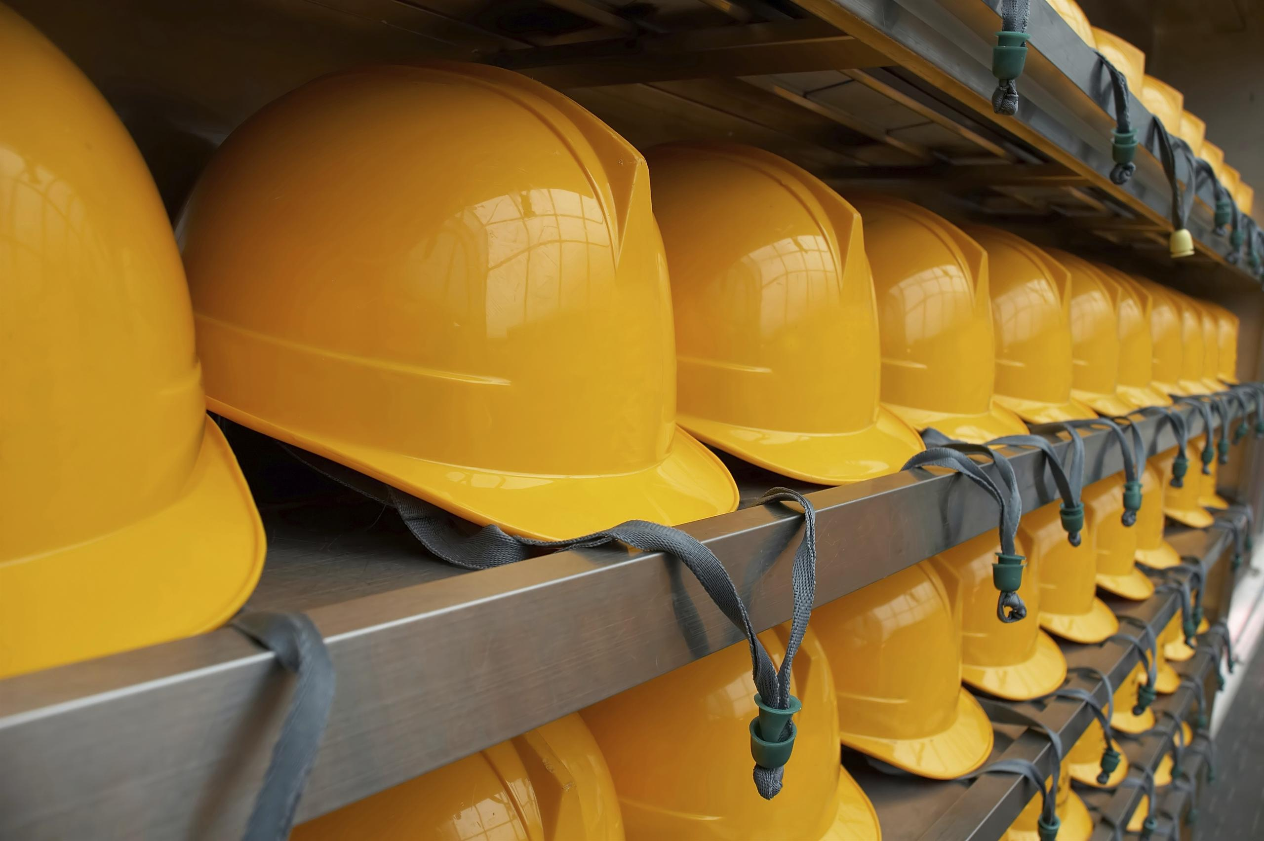 image showing rows of hard hats on shelves