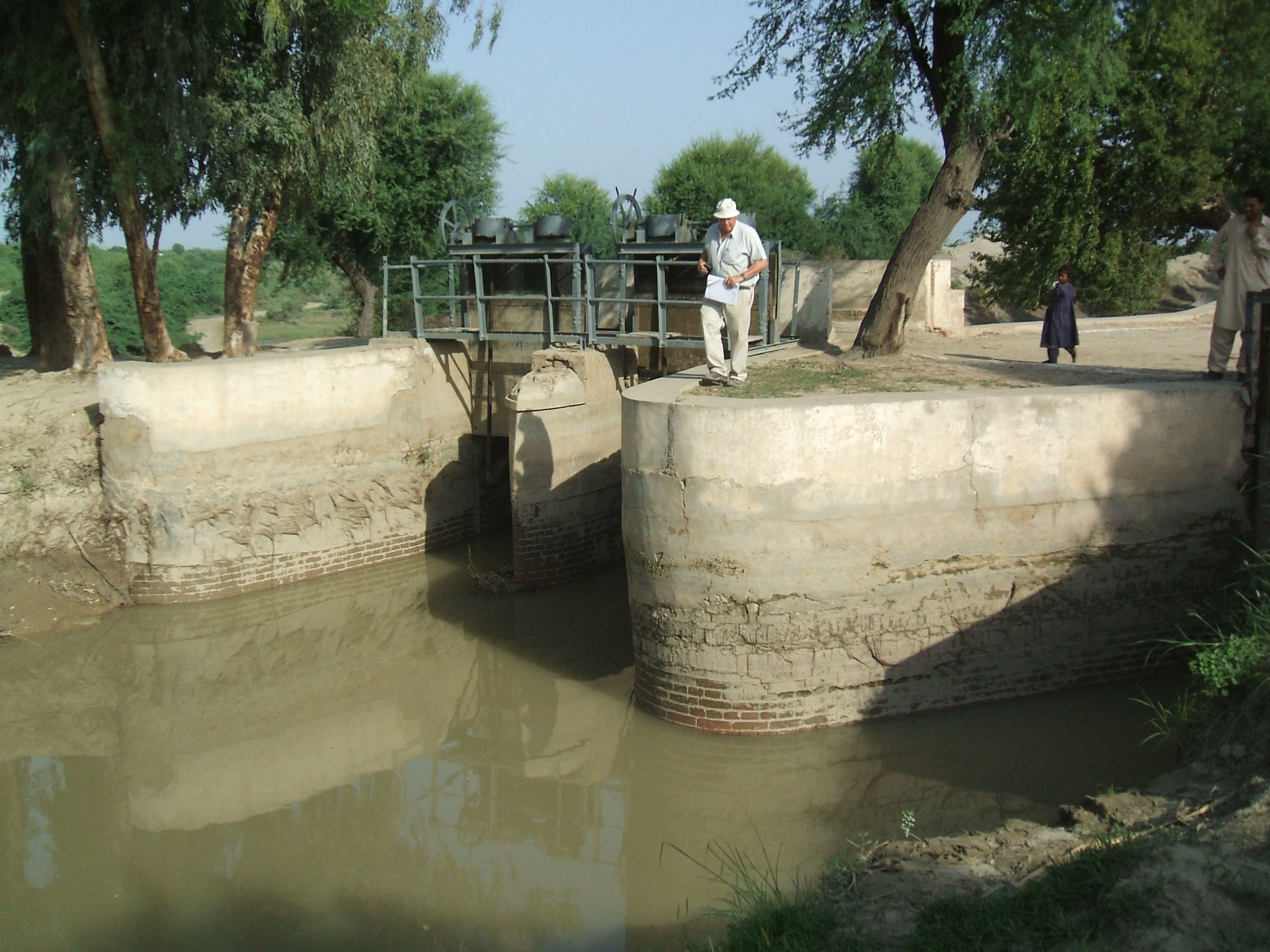 Man checking condition of canal sluice gates.