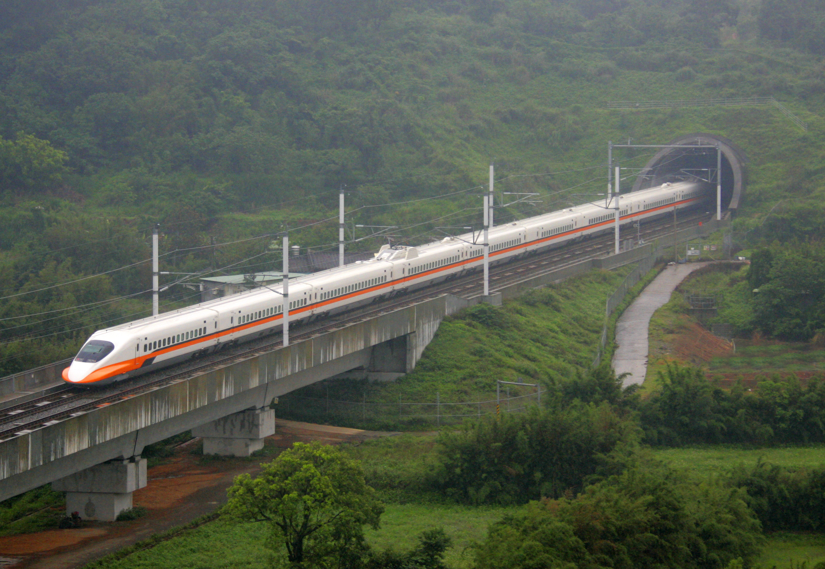 High speed train exiting tunnel approaching viaduct