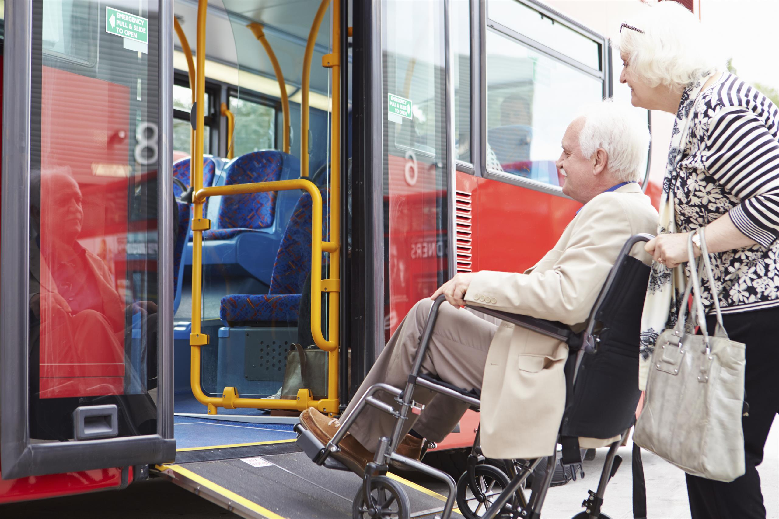 Man in a wheelchair getting support to get onto a bus
