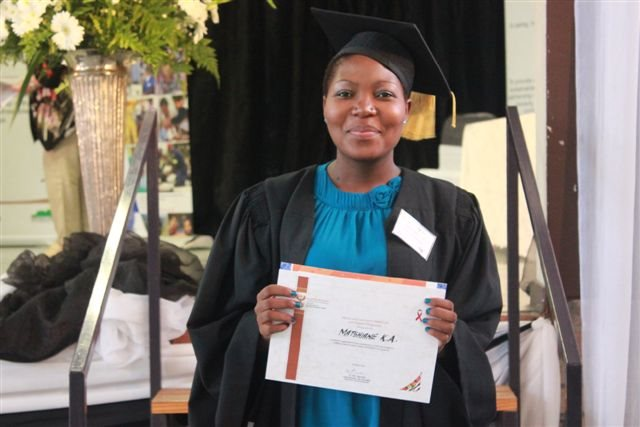 Community caregiver holds up Thogomelo training certificate at graduation