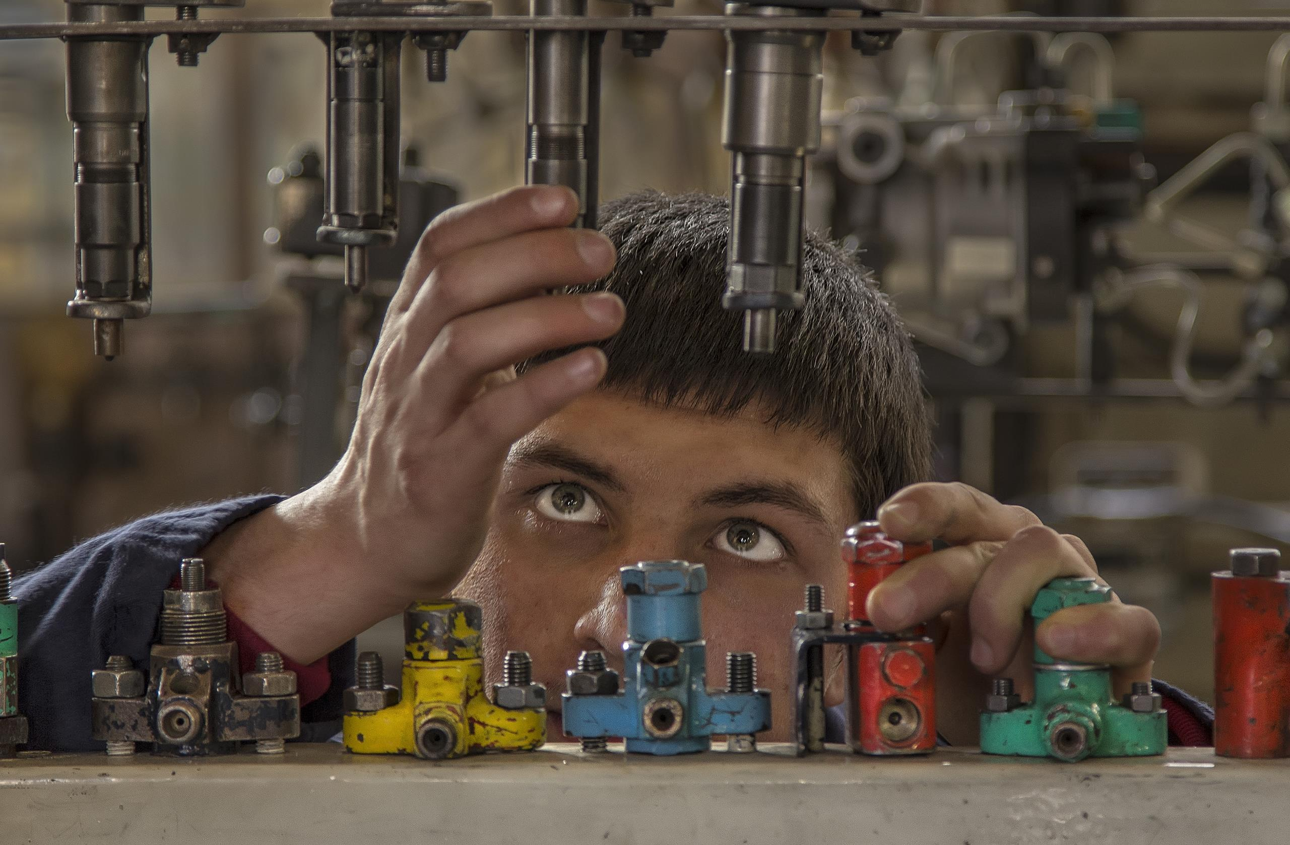 Young man working with machinery in workshop