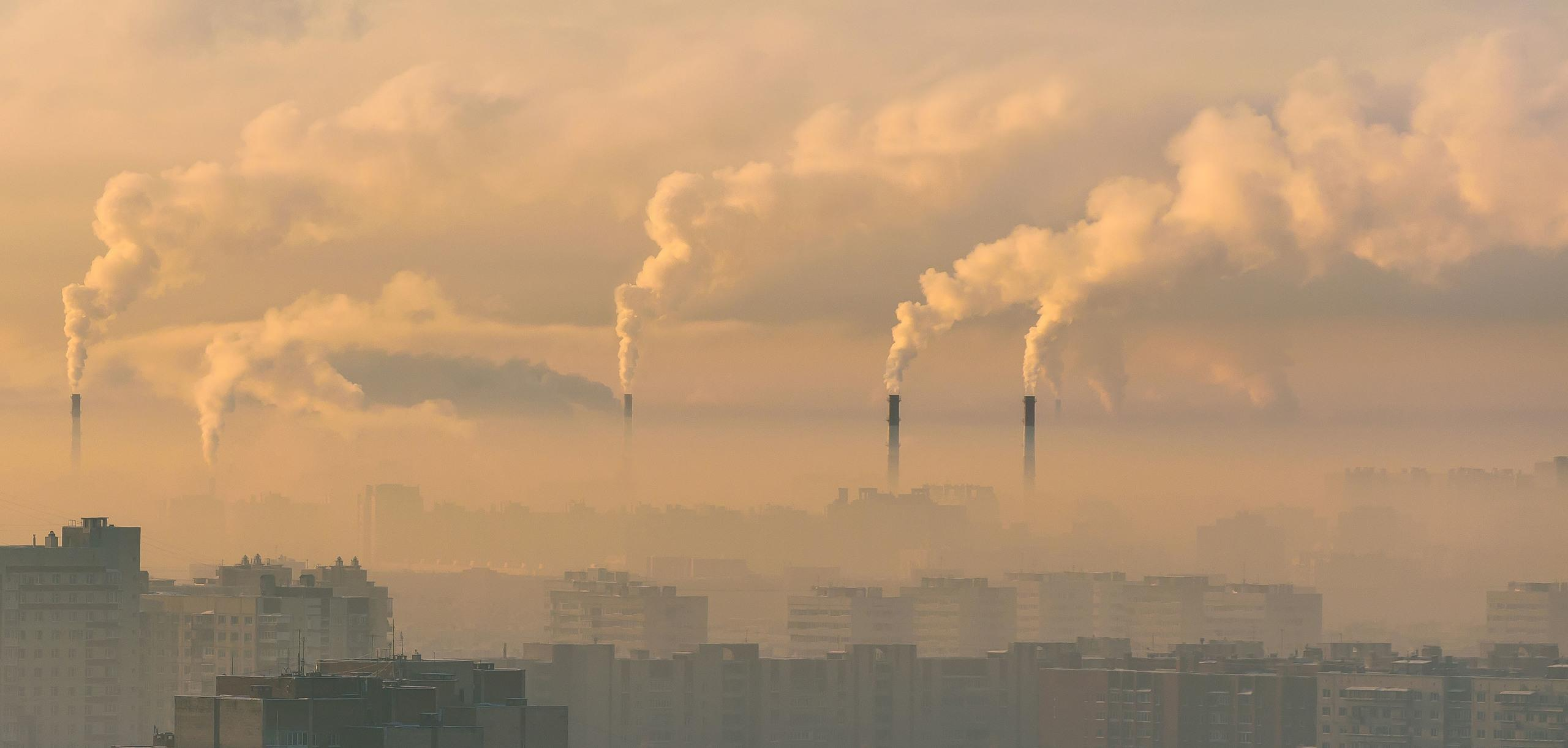 An urban skyline with pollution going into the atmosphere from the chimneys at a power plant