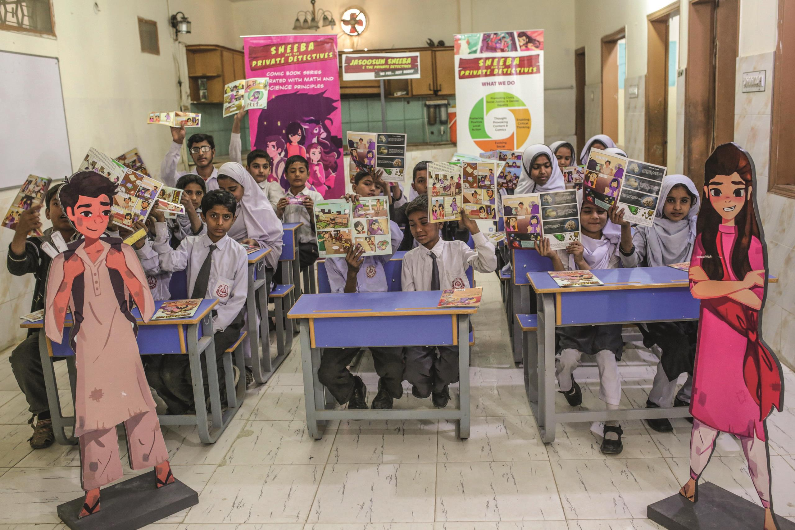 Students holding up open pages of the AzCorp Sheeba comic book as part of The Pakistan Education Innovation Fund.