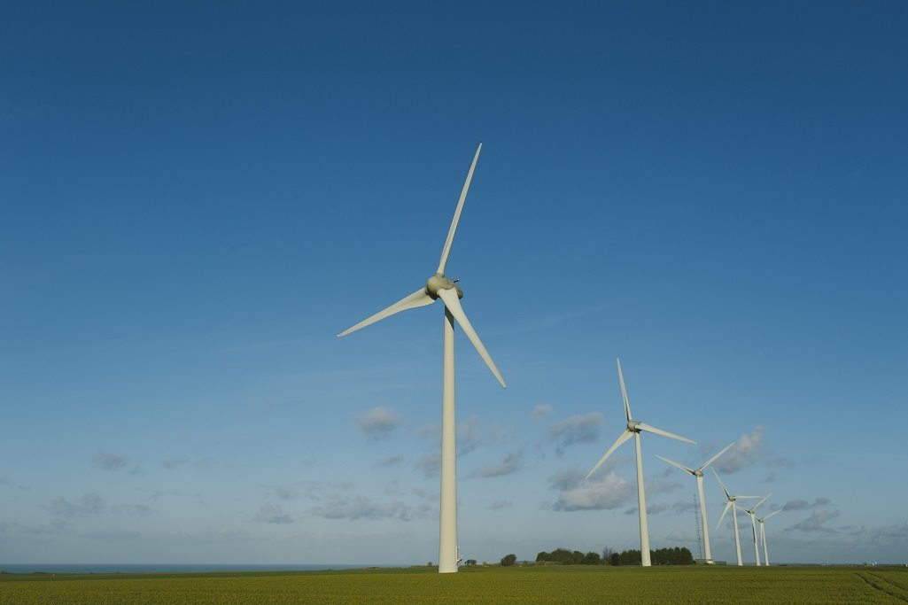 An onshore wind farm in France. The wind farm of five turbines is on green grass and in front of blue sky.