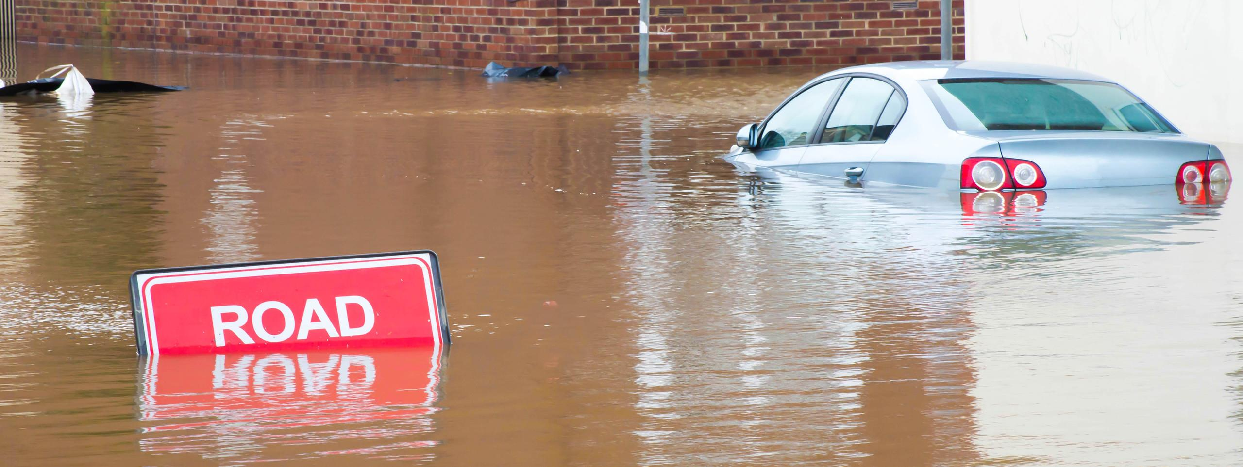 A road sign and car submerged under water caused by a flood in York