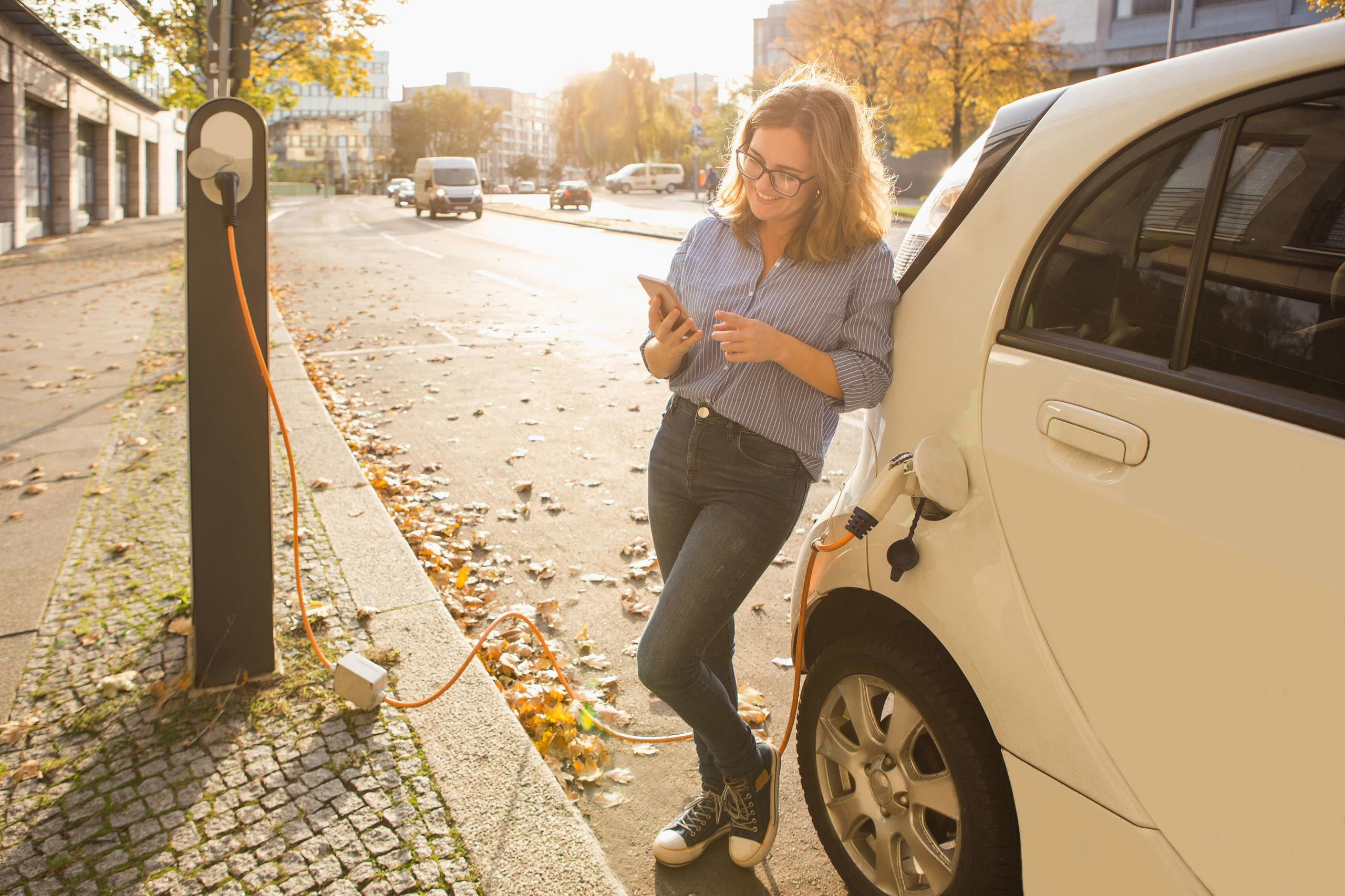 A young woman using her mobile phone whilst waiting for her electric car to charge.