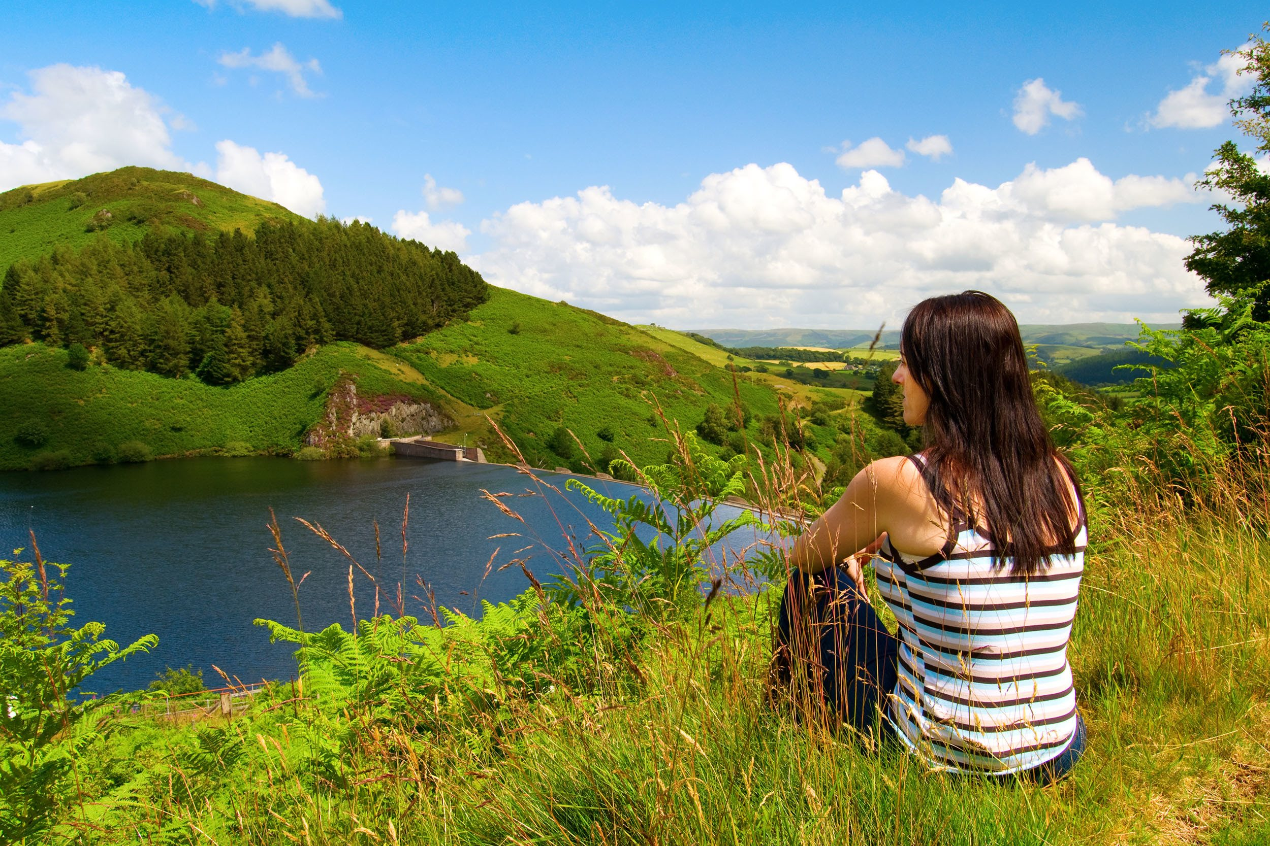 A woman sat looking over the Llyn Clywedog Reservoir